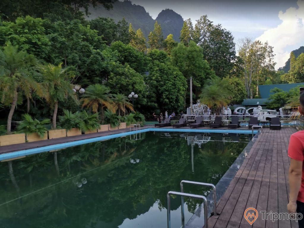 Bể tắm ngoài trời tại khu du lịch sinh thái Trường Xuân, cây cối xanh tươi gần bể tắm, bầu trời có mây, ảnh chụp ngoài trời
