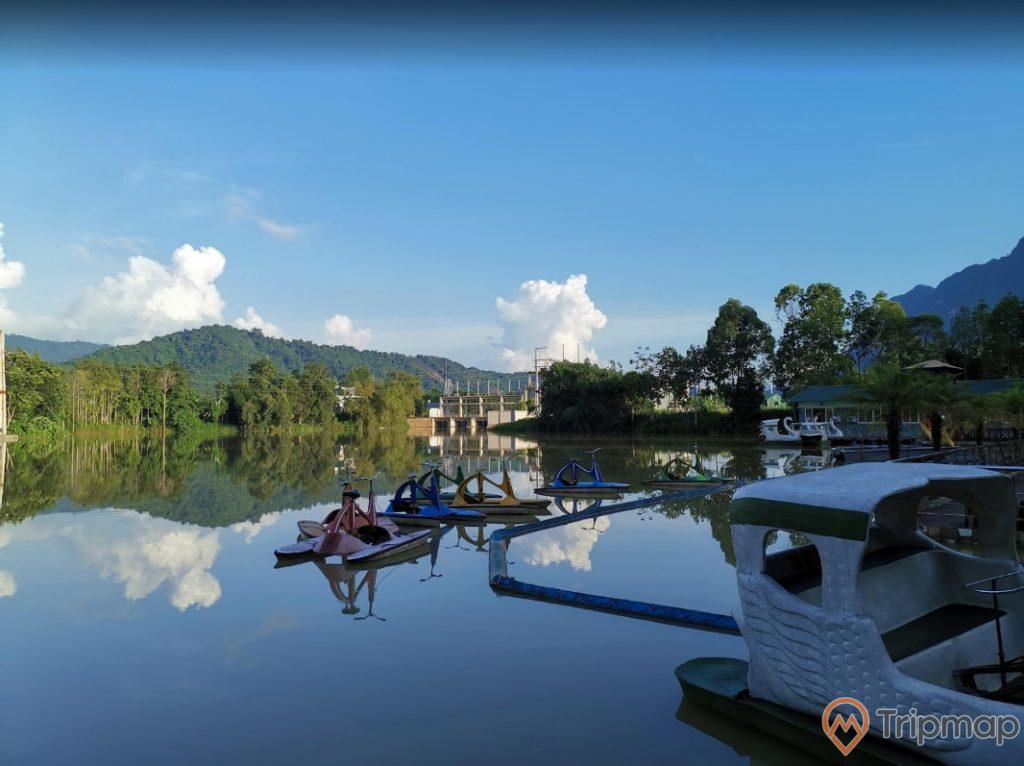 Cảnh quan thiên nhiên tại khu du lịch sinh thái Trường Xuân, xe đạp dưới nước trên mặt hồ, cây cối xanh tươi ven hồ nước, đồi núi phía xa xa, bầu trời trong xanh có mây, ảnh chụp ngoài trời