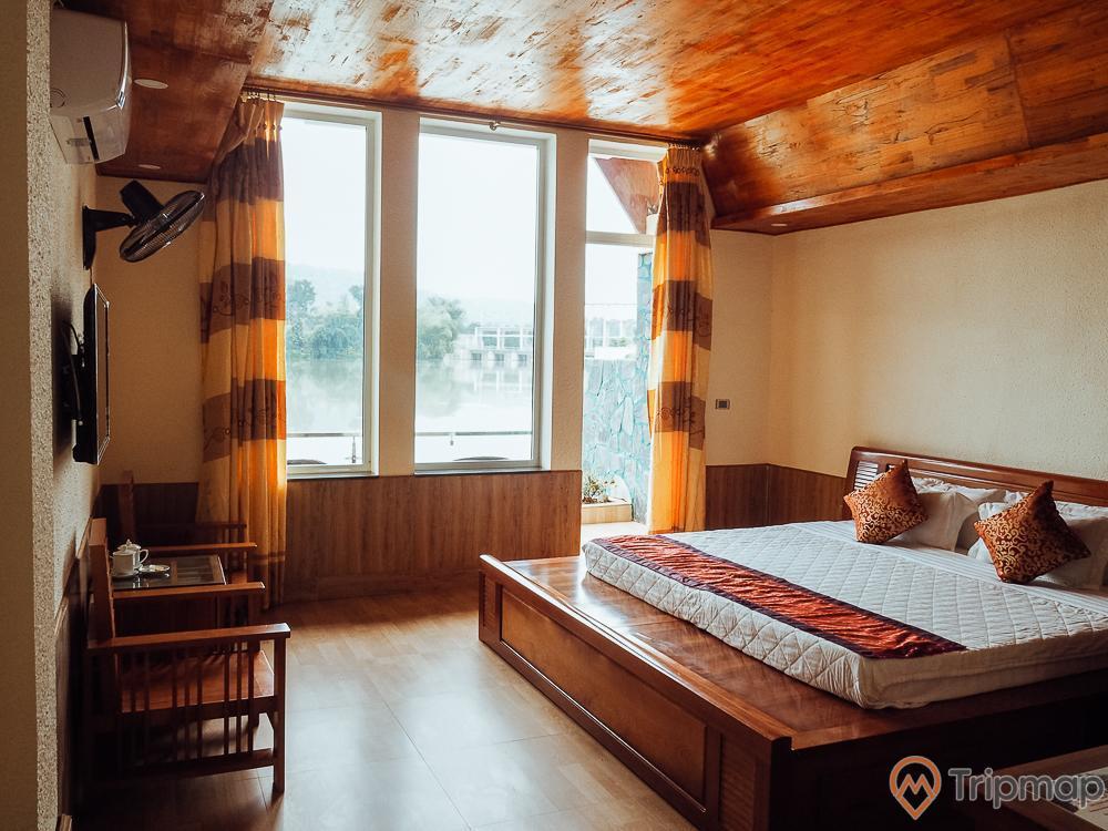 Phòng nghỉ ngơi ở khách sạn tại khu du lịch sinh thái Trường Xuân, đồ đặc trong phòng xếp gọn gàng, chiếc gối trên đệm màu trắng đặt trên giường bằng gỗ, cái quạt và tivi treo trên trường phía trên bộ bàn ghế, rèm cửa màu nâu vàng, cửa sổ kính, ảnh chụp trong nhà
