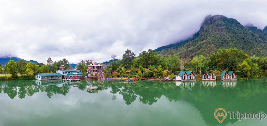 Cảnh quan thiên nhiên tại khu du lịch sinh thái Trường Xuân, ngôi nhà bên hồ nước, cây cối xanh tươi và đồi núi gần hồ nước, bầu trời nhiều mây, ảnh chụp ngoài trời