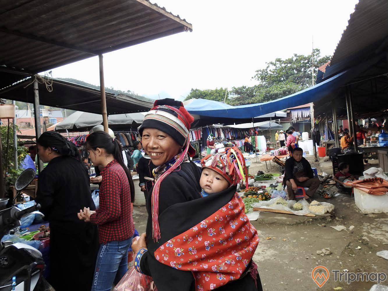 Chợ phiên ở ruộng bậc thang Hoàng Su Phì, người phụ nữ tươi cười địu con trên lưng, hàng quán buôn bán tại chợ phiên, bầu trời nhiều mây, ảnh chụp ngoài trời