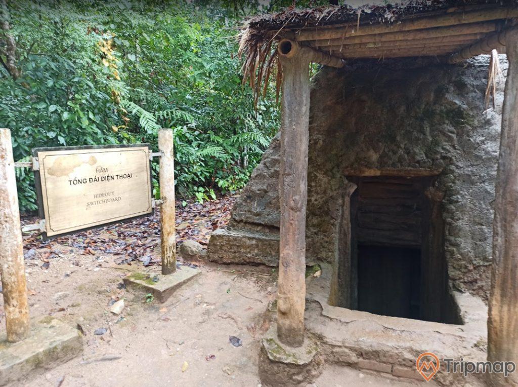 hầm tổng đài điện thoại tại sở chỉ huy chiến dịch Điện Biên Phủ, cây cối xanh tươi phía sau căn hầm, tấm bảng thông tin màu vàng nhạt, ảnh chụp ngoài trời