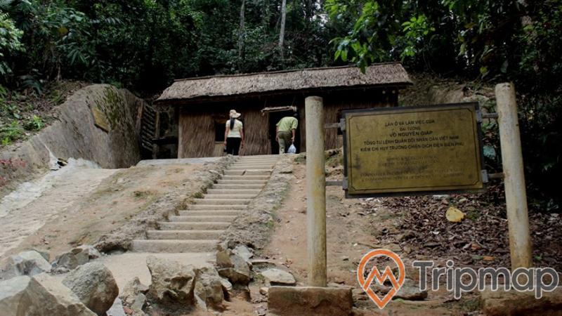 lán ở và làm việc của đại tướng Võ Nguyên Giáp ở sở chỉ huy chiến dịch Điện Biên Phủ, tấm bảng thông tin địa điểm, cây cối xanh tươi gần ngôi nhà, bậc thang đi lên ngôi nhà