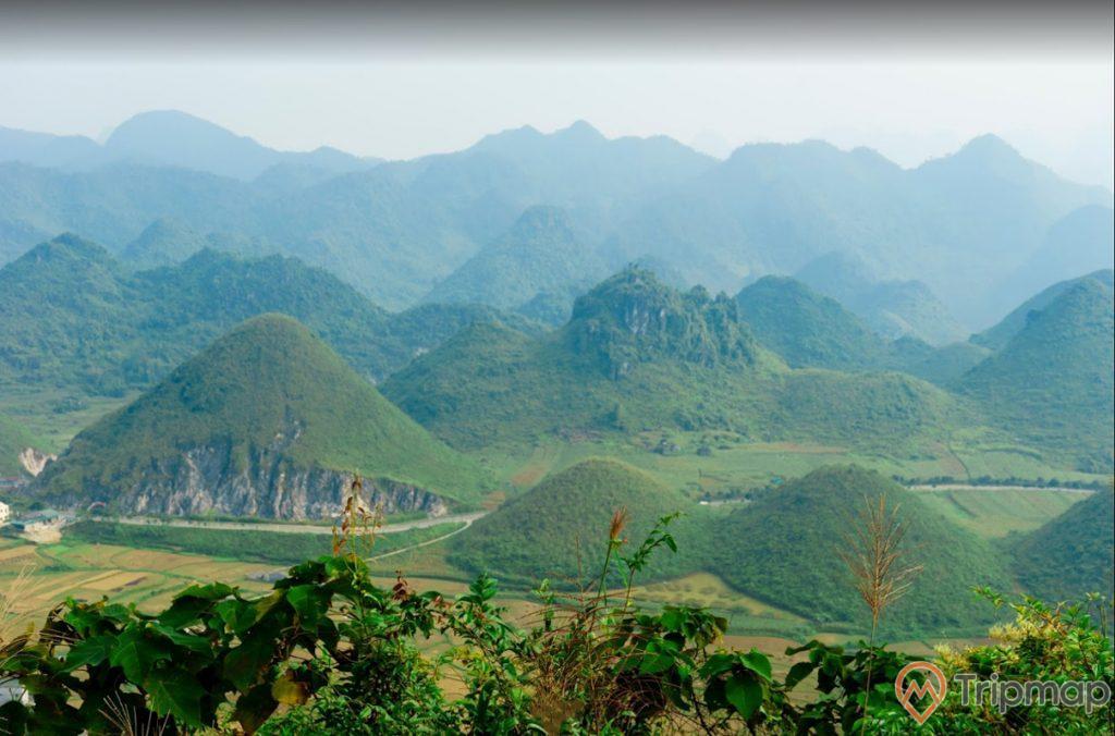 Vẻ đẹp thiên nhiên tại thắng cảnh núi đôi Quản Bạ, cỏ cây xanh tươi, đồi núi phía xa xa, bầu trời nhiều mây, ảnh chụp trên cao