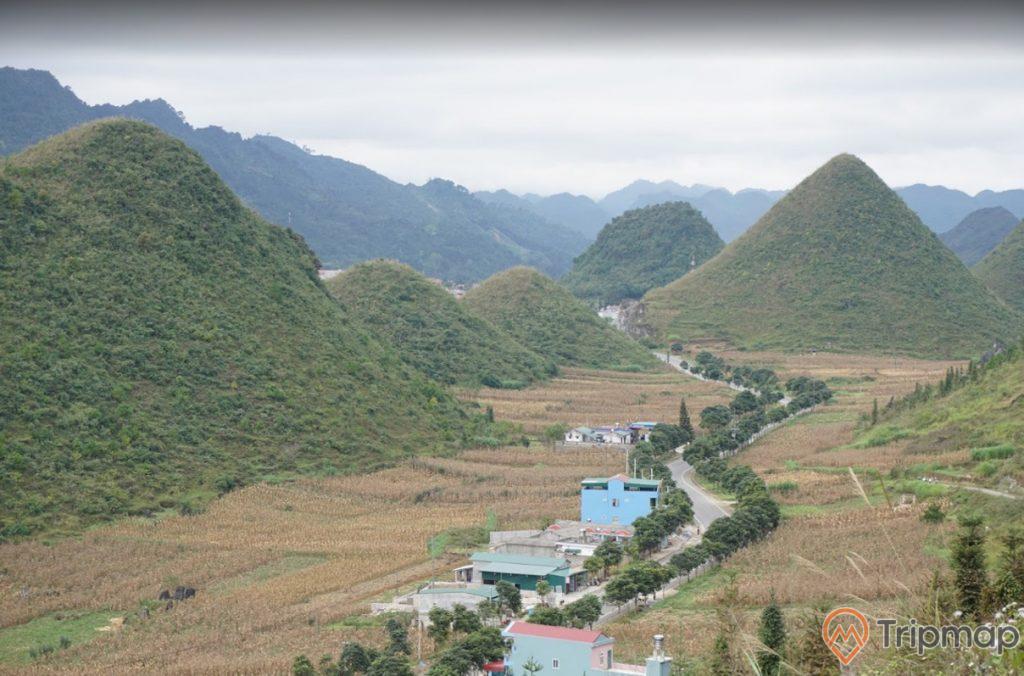 Quang cảnh thiên nhiên tại thắng cảnh núi đôi Quản Bạ, đồi núi cỏ cây xanh tươi, ngôi nhà gần địa danh núi đôi, bầu trời nhiều mây, ảnh chụp ngoài trời