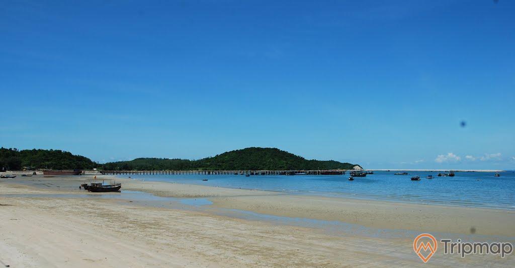 Bãi tắm Minh Châu, bờ cát vàng trải dài, mặt nước biển màu xanh, ngọn núi nhiều cây xanh ở phía xa, trời xanh, ảnh chụp ban ngày
