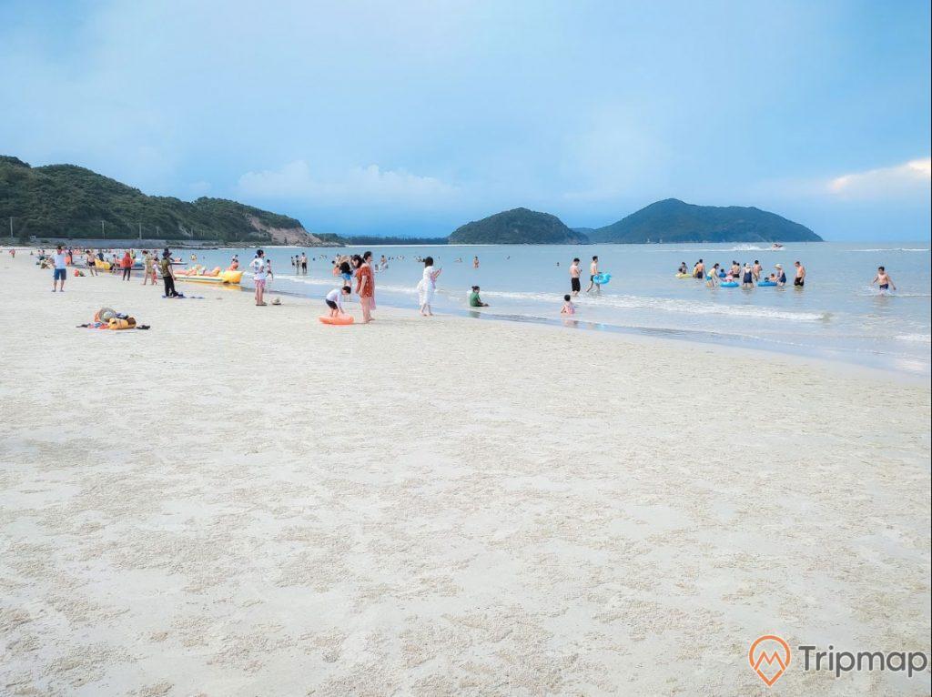 Bãi tắm Quan Lạn, bãi cát màu trắng, nhiều người đang tắm biển, nhiều ngọn núi đá phía xa, trời xanh, ảnh chụp ban ngày