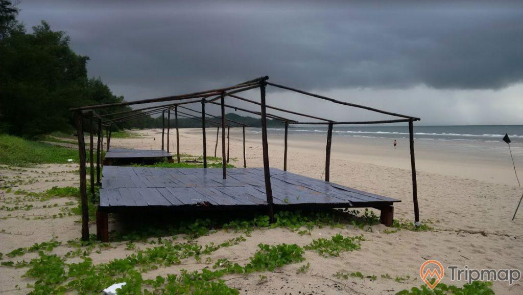 Bãi tắm Quan Lạn, bãi cát màu trắng trải dài, tấm gỗ màu đen, trời nhiều mây đen, ảnh chụp buổi chiều
