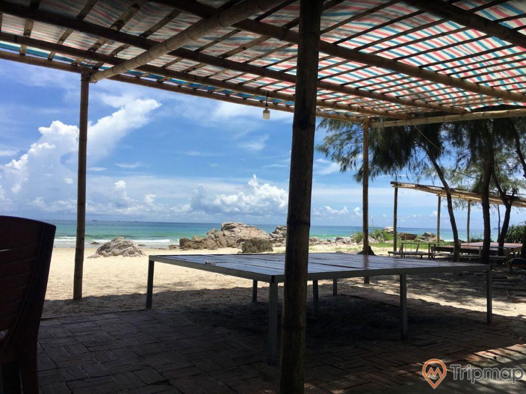 Bãi tắm Robinson, trời nắng, bãi biển có bờ cát trắng, nhiều tảng đá to màu xám, cái bàn gỗ, ảnh chụp ban ngày