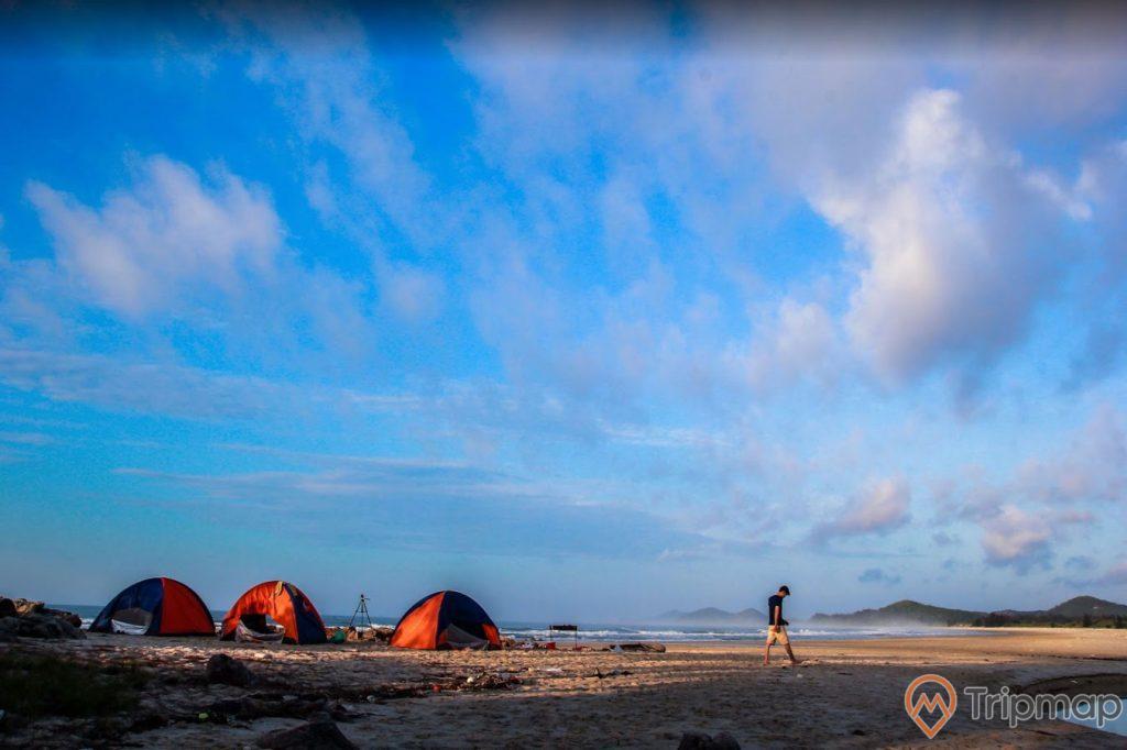 Bãi tắm Sơn Hào, trời xanh nhiều mây, người đang đi trên bãi cát, bãi cát màu trắng, nhiều lều màu cam, ảnh chụp ban ngày