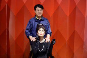 Bảo tàng tượng sáp, tượng sáp người phụ nữ mặc áo đen, người đàn ông mặc áo xanh đứng sau đang đặt tay lên tượng sáp, bức tường đằng sau màu đỏ
