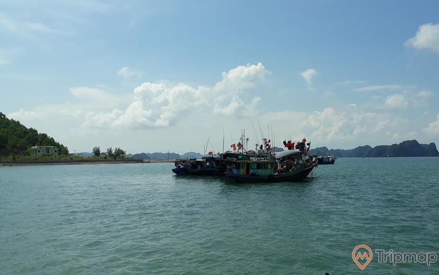 Bến Cống Yên, thương cảng cổ Vân Đồn, thuyền đang chạy trên biển, mặt nước biển màu xanh, ngọn núi đá phía xa, trời xanh, nhiều mây, ảnh chụp ban ngày