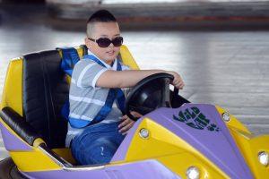 Bò sát đụng độ, em bé đeo kính đang lái xe, nền gạch màu xám