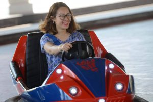 Bò sát đụng độ, cô gái đeo kính mặc áo xanh đang lái xe điện, xe điện màu xanh