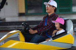 Bò sát đụng độ, người đàn ông đội mũ trắng và cô bé đội mũ hồng đang cười, 2 người đang lái chiếc xe màu vàng