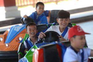 Bò sát đụng độ, các em bé đang lái xe điện, em bé mặc áo trắng đang cười, em bé đội mũ đỏ