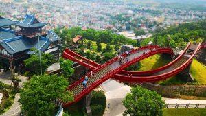 Cầu Koi, cầu sơn màu đỏ, nhiều người đang đi trên cầu, nhiều cây xanh, khu dân cư ở phía xa, nhà có mái ngói màu xám, ảnh chụp từ trên cao, ảnh chụp ban ngày