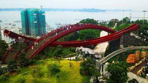 Cầu Koi, cầu sơn màu đỏ, nhiều người đang đi trên cầu, thảm cỏ màu xanh, nhiều cây xanh, tòa nhà đang được xây dựng ở phía xa, ảnh chụp ban ngày