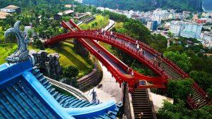 Cầu Koi, cầu sơn màu đỏ, mái ngói màu xanh, nhiều người đang đi trên cầu, nhiều cây xanh, khu dân cư ở phía xa, ảnh chụp ban ngày, ảnh chụp từ trên cao