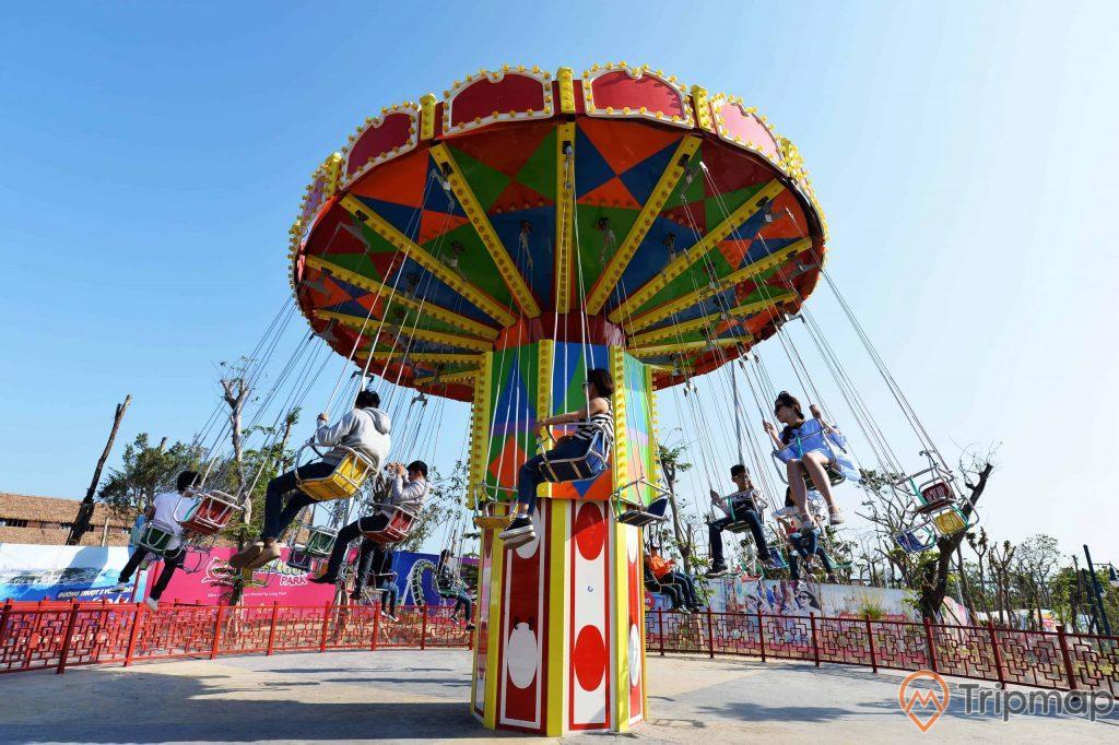 Chiếc Ô Kỳ Diệu, trụ quay nhiều màu sắc, nhiều người đang ngồi trên đu quay, trời nắng, ảnh chụp ban ngày