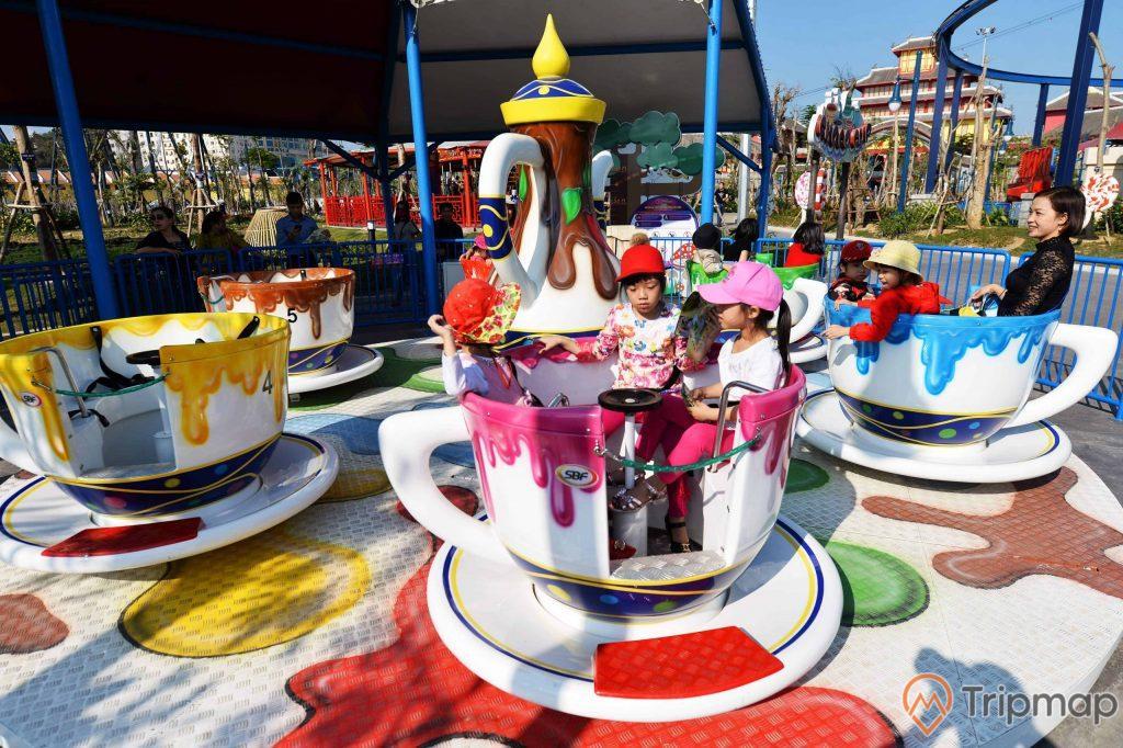 Choco-Cups, Chiếc Cốc Thần, nhiều mô hình cốc màu trắng, hàng rào sơn màu xanh, nhiều người đang ngồi trong mô hình cốc, trời nắng, ảnh chụp ban ngày