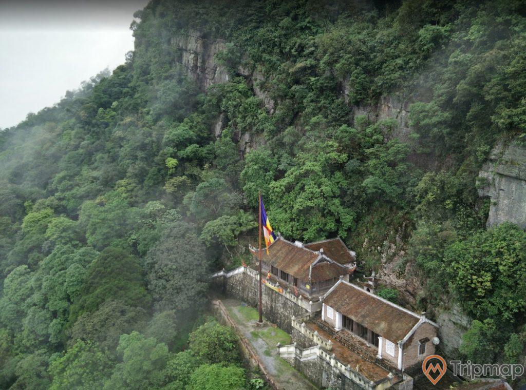 Chùa Bảo Sái, chùa sơn màu nâu, mái ngói màu nâu, nhiều cây xanh, ngọn núi đá to có cây xanh, ảnh chụp từ trên cao , ảnh chụp ban ngày