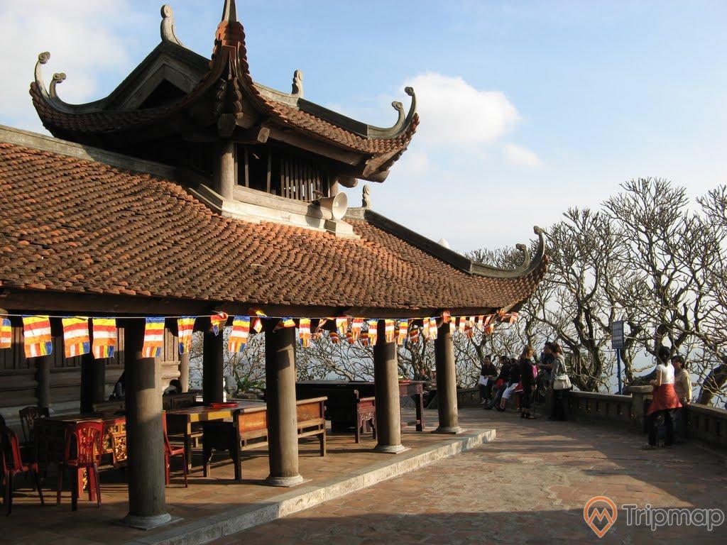 Chùa Hoa Yên, Yên Tử, nền gạch màu đỏ, mái ngói màu đỏ, nhiều cây cột trụ, nhiều người đang vãn cảnh, nhiều cây xanh, trời xanh, ảnh chụp ban ngày, ảnh chụp trời nắng