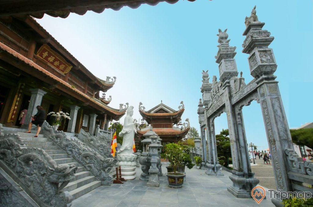 Chùa Trình, Yên Tử, tượng phật bằng đá, bậc thang bằng đá màu xám, trời xanh, nhiều chậu cây, ảnh chụp ban ngày