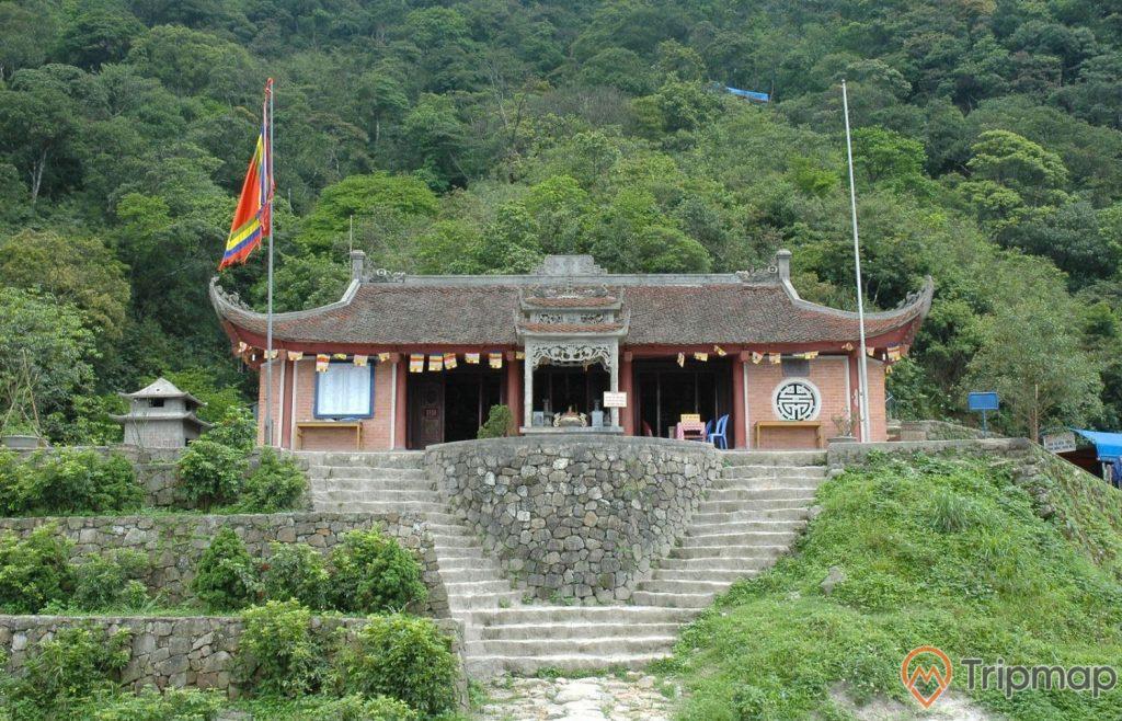 Chùa Vân Tiêu, bậc thang màu xám, nhiều cây xanh, ngọn núi phía sau, mái ngói màu nâu, ảnh chụp ban ngày
