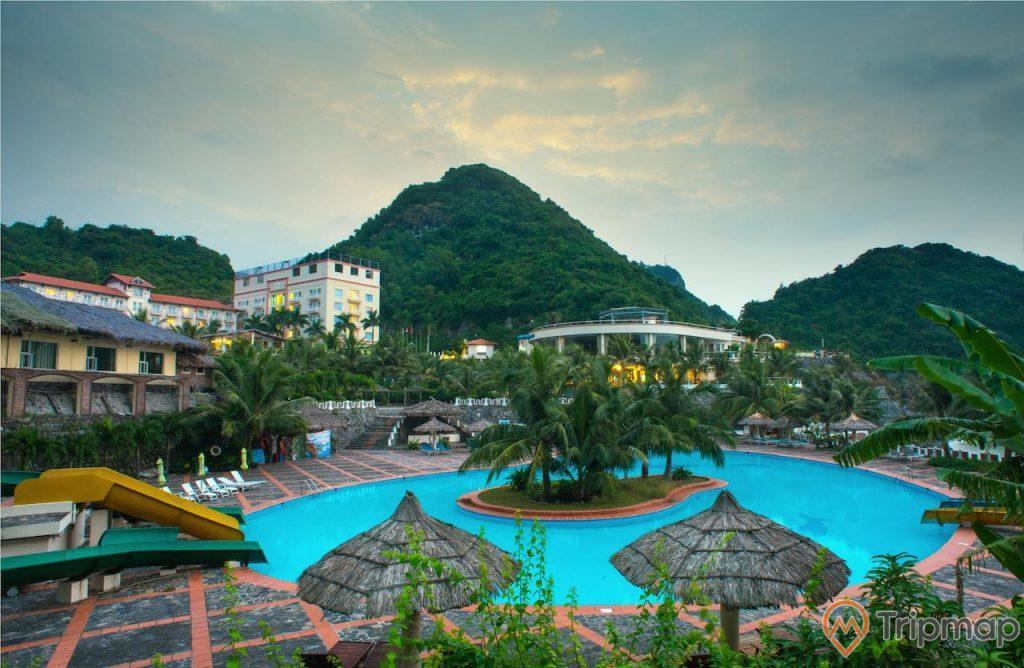 Resort , bể bơi, nhiều cây xanh, cầu trượt, nền gạch màu đỏ đen, khu nghỉ dưỡng, nhiều ngọn núi phía xa, trời nhiều mây, ảnh chụp ban chiều