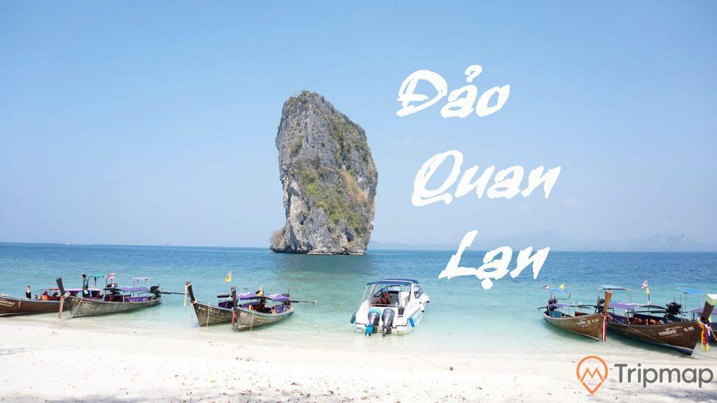 Đảo Quan Lạn, nhiều thuyền đang đỗ trên mặt nước, bãi cát trắng, nước biển màu xanh, ngọn núi đá có cây xanh ở phía xa, trời xanh, ảnh chụp ban ngày