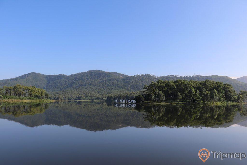 Hồ Yên Trung, mặt hồ trong, nhiều cây xanh, ngọn núi ở phía xa, ảnh chụp ban ngày