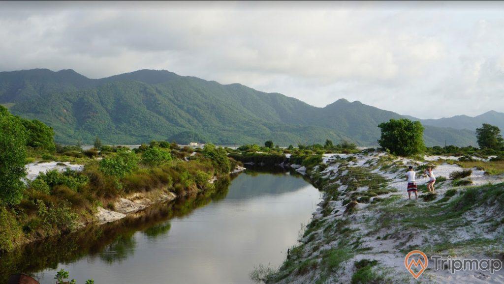 Đồi cát pha lê, bờ sông, người mặc áo trắng đang đứng trên cát, ngọn núi nhiều cây xanh ở phía xa, trời nhiều mây, ảnh chụp ban ngày
