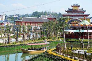 Du thuyền nhiệt đới, nhiều cây xanh, hàng rào sắt sơn màu nâu, trời nắng, thuyền chở người chạy trên sông, ảnh chụp ban ngày