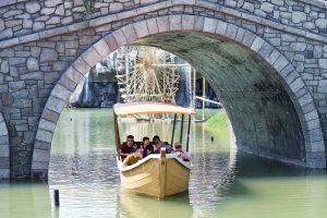 Du thuyền nhiệt đới, nhiều người đang ngồi trên thuyền, thuyền màu vàng chạy trên nước, trời nắng, cây cầu bằng đá màu xám, ảnh chụp ban ngày