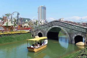 Du thuyền nhiệt đới, thuyền chờ nhiều người chạy trên sông, cầy cầu đá màu xám, thuyền màu vàng, tòa nhà cao tầng ở phía xa, trời nắng, ảnh chụp ban ngày, vườn hoa bên cạnh sông