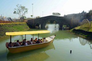 Du thuyền nhiệt đới, thuyền chở nhiều người chạy trên sông, cây cầu bằng đá màu xám, trời nắng, ảnh chụp ban ngày