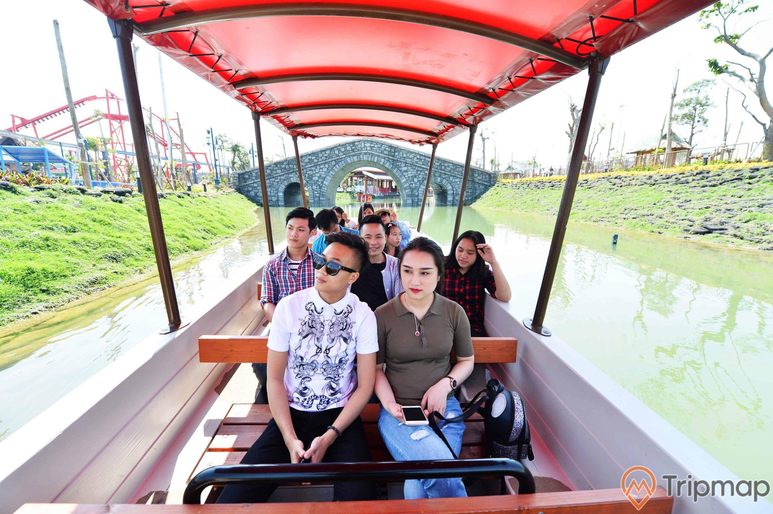 Một du thuyền nhỏ xinh xắn trên dòng sông êm đềm, du khách đang trong thuyền trên mặt sông, hai bên bờ sông cỏ xanh tươi, ảnh chụp ban ngày trời nắng