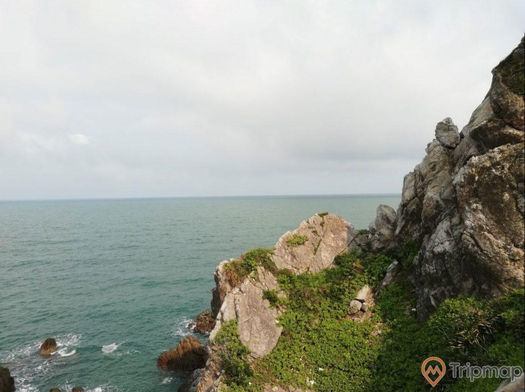 Eo Gió Gót Beo, tảng đá to màu xám có cây xanh, nước biển màu xanh, trời nhiều mây, ảnh chụp ban ngày