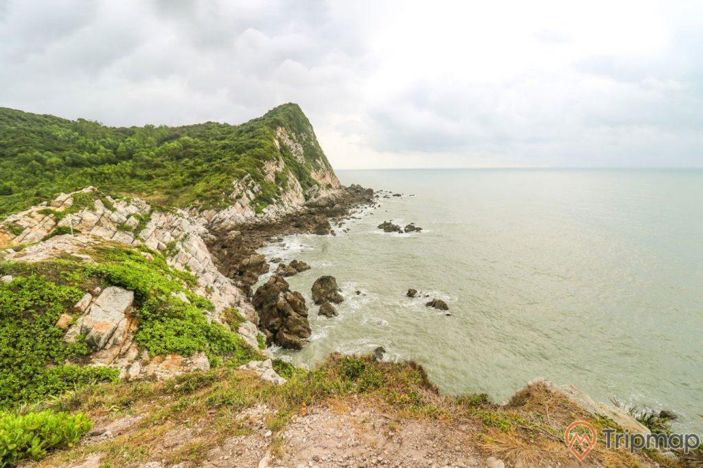 Eo Gió Gót Beo, nước biển màu xanh, ngọn núi đá có cây xanh, trời nhiều mây, ảnh chụp ban ngày