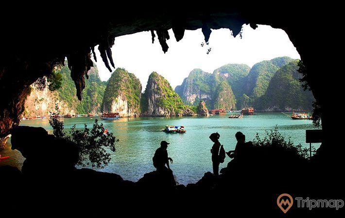 Hang Bồ Nâu, vịnh Hạ Long, người trong hang, nhiều thuyền đang chạy trên biển, mặt nước biển màu xanh, nhiều ngọn núi đá có cây xanh phía xa, ảnh chụp ban ngày