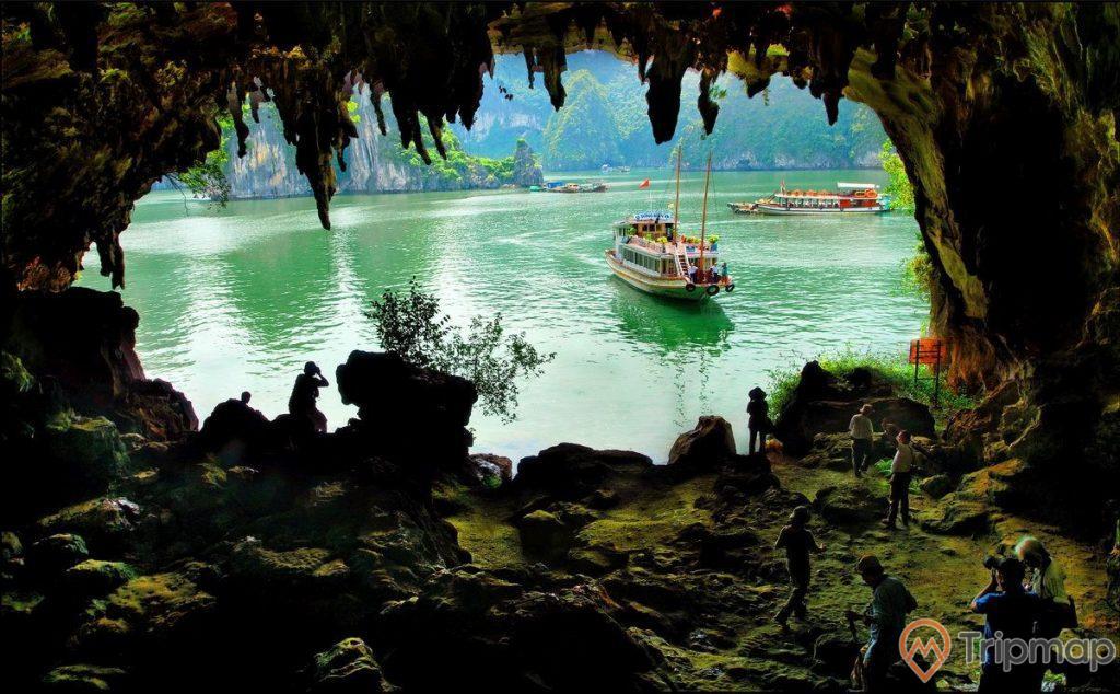 Hang Bồ Nâu, vịnh Hạ Long, ảnh chụp từ trong hang, khách du lịch đang tham quan hang, thuyền chạy trên biển, mặt nước biển màu xanh, nhiều ngọn núi đá phía xa, ảnh chụp ban ngày