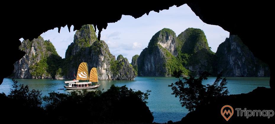Hang Trống, vịnh Hạ Long, thuyền buồm, cánh buồm màu cam, mặt nước biển màu xanh, nhiều ngọn núi đá có cây xanh phía xa, ảnh chụp ban ngày