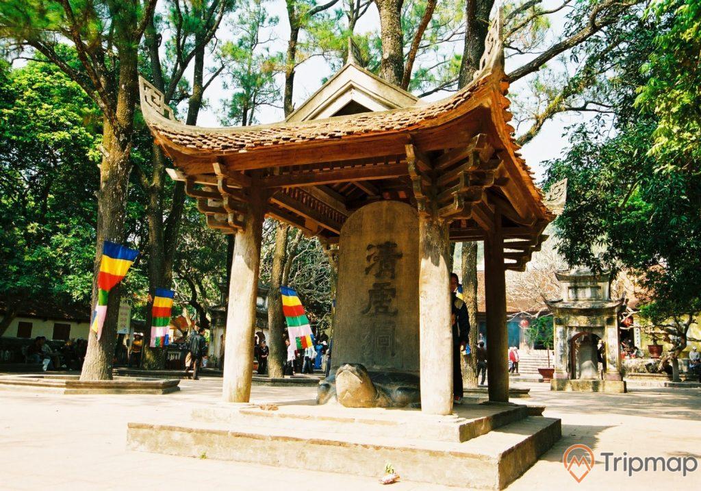 Bia Thanh Hư Động, bia bằng đá màu xám có chữ hán, con rùa bằng đá, mái ngói màu đỏ, nhiều lá cờ, cây xanh xung quanh, ảnh chụp ban ngày, trời nắng