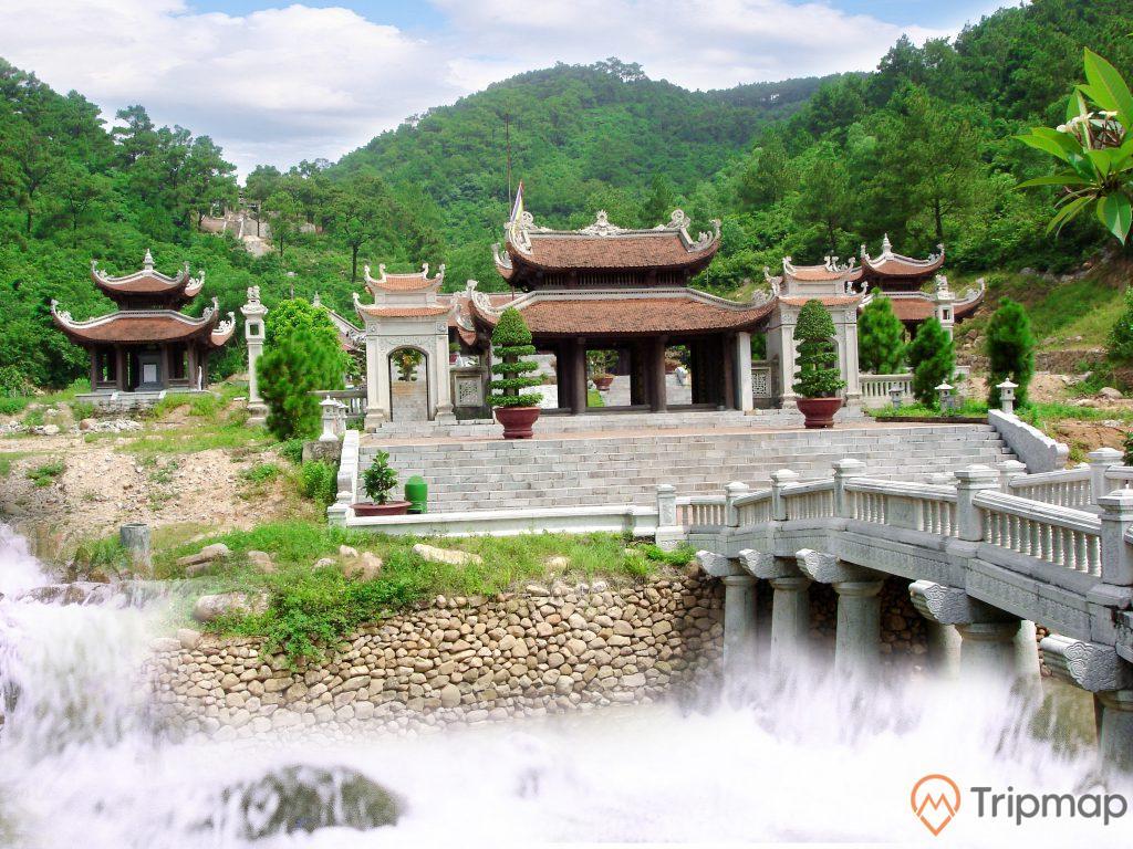 Khu di tích Côn Sơn, cây cầu màu xám, bậc thang màu xám, chậu cây màu đỏ, nhiều cây xanh, ngọn núi phía xa, trời xanh nhiều mây, ảnh chụp ban ngày