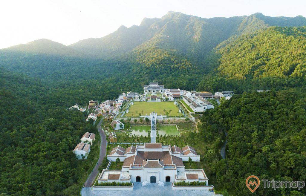 Khu di tích thắng cảnh Yên Tử, nhiều cây xanh, nhiều mái ngói đỏ, di tích sơn màu trắng, ngọn núi to nhiều cây xanh ở phía xa, ảnh chụp trời nắng, ảnh chụp ban ngày, ảnh chụp từ trên cao