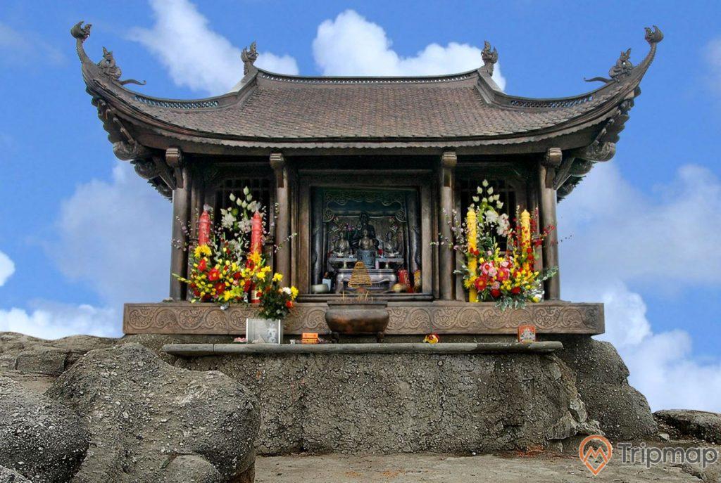 Chùa Đồng, Yên Tử, tảng đá màu xám, lư hương, nhiều bó hoa, mái ngói màu nâu, ảnh chụp ban ngày, trời xanh, nhiều mây, nền đất màu nâu