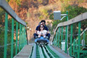 Khu làn trượt Samurai, Dragon Park, đường ray sơn màu xanh, 2 người đang ngồi trên ghế trượt, ngọn núi phía sau, trời nắng, ảnh chụp ban ngày