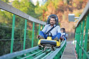 Khu làn trượt Samurai, đường ray sơn màu xanh, người đàn ông đang ngồi trên ghế trượt màu vàng, cây xanh phía sau, ảnh chụp ban ngày