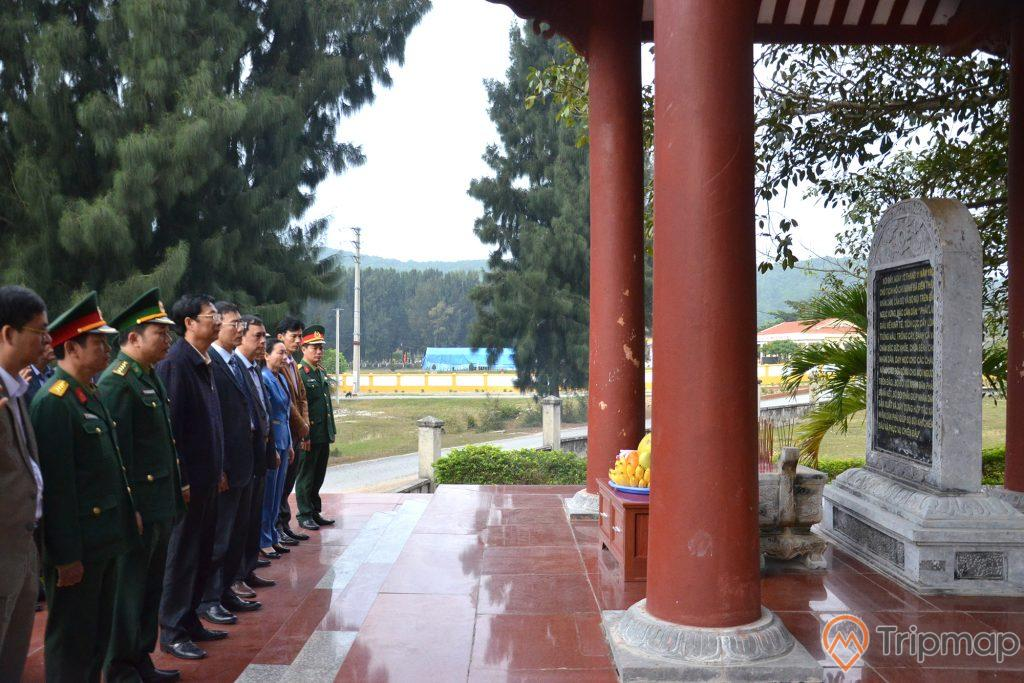 Khu lưu niệm Bác Hồ, nhiều sĩ quan đang đứng trên nền gạch màu đỏ, cây cột màu đỏ, bia đá, nhiều cây xanh, ảnh chụp ban ngày